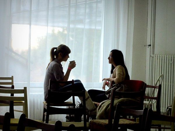 two women talking privately in room image