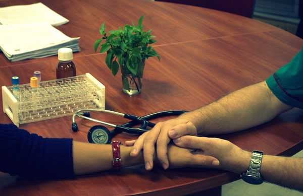 compassion docter holding hands on table