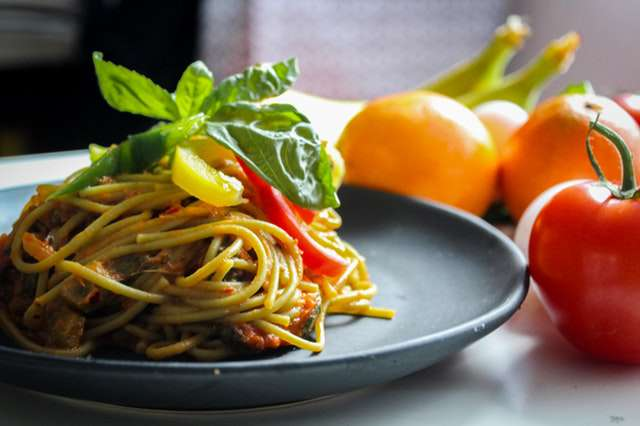 pasta-with-vegetable-dish-on-gray-plate-beside-tomato-fruit img