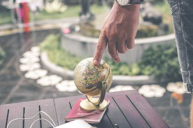 person-holding-terrestrial-globe-scale