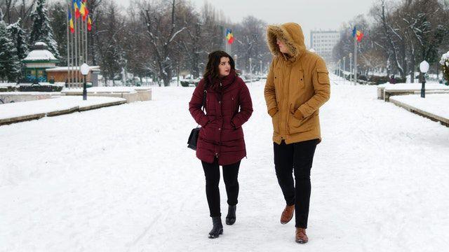 man-in-brown-parka-jacket-walking-beside-woman-in-maroon