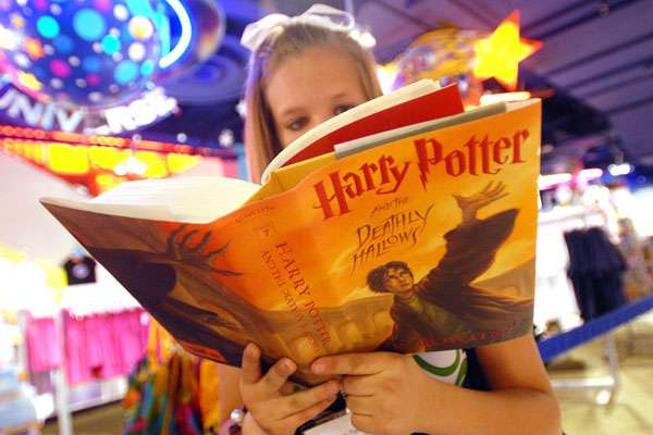 girl reading Harry Potter And The Deathly Hallows book img