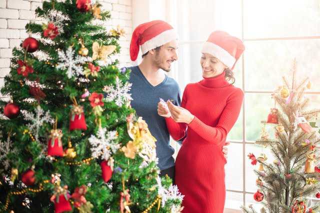 man-and-woman-standing-beside-christmas-tree
